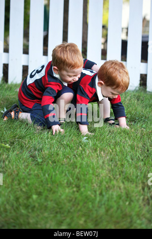 Twin baby boys playing outside - Stock Photo