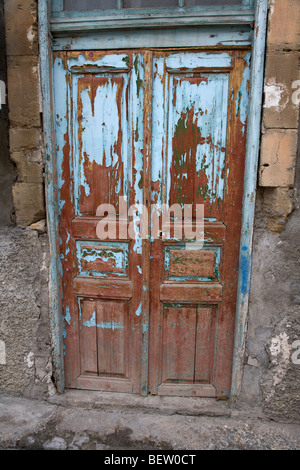 flaking painted wooden door with numerous layers of old paint in a crumbling old building. greek turkish cypriot - Stock Photo