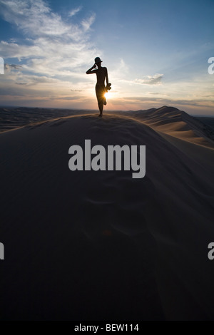 Silhouette of a native nomad man standing on top of sand dunes in the Gobi desert at sunset. Khongoryn Eels, Mongolia - Stock Photo