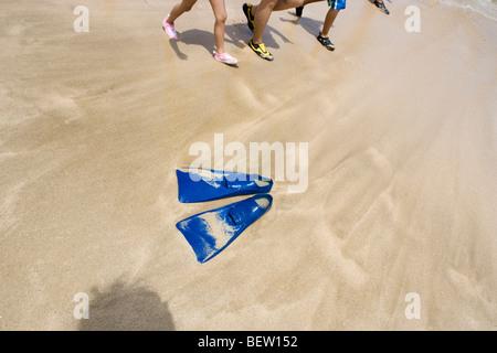 scuba gear flippers left on the beach, kids walking along - Stock Photo
