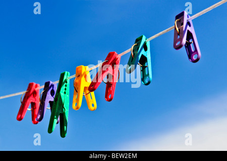 Colorful clothes pegs on line against blue sky - Stock Photo