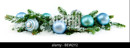 Many Christmas decorations laying in pine branches and snow - Stock Photo