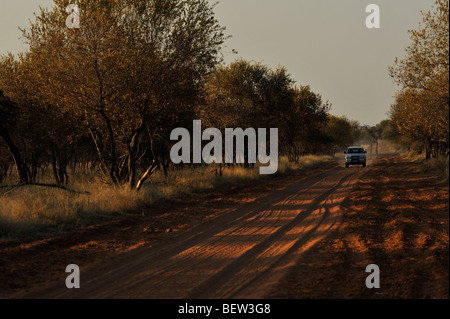 4x4 off road truck on dirt road in African savanna - Stock Photo