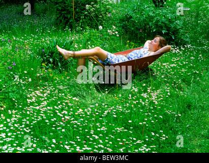 Girl resting in wheelbarrow in yard filled with bellis flowers - Stock Photo