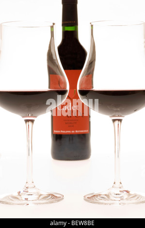 Two filled claret glasses in front of wine bottle, low angle view - Stock Photo