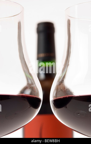 Two filled claret glasses in front of wine bottle, cross-section - Stock Photo