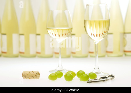 Two filled white wine glasses in front of a row of wine bottles, still life - Stock Photo