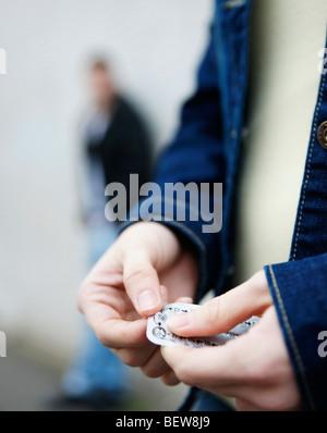 Teenage girl unpacking birth control pill - Stock Photo
