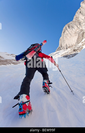 Person climbing on a snowy mountain skis, Berchtesgaden, Germany, low angle view - Stock Photo