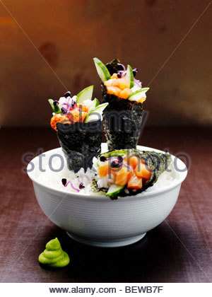 Three Temaki Sushi rolls in a rice bowl, close-up - Stock Photo