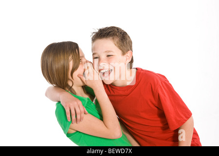 girl whispering something in a boy's ear - Stock Photo