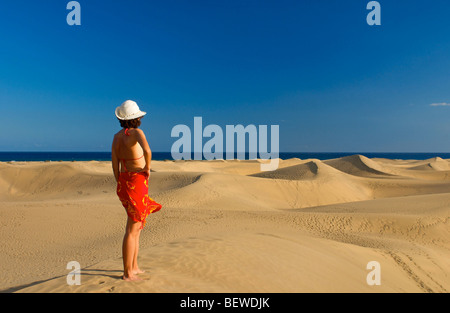 Woman standing on a sand dune looking at the sea, Maspalomas, Gran Canaria, Spain, rear view - Stock Photo