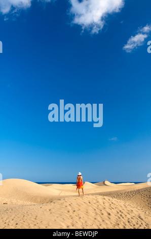 Woman standing on a sand dune, Maspalomas, Gran Canaria, Spain, rear view - Stock Photo