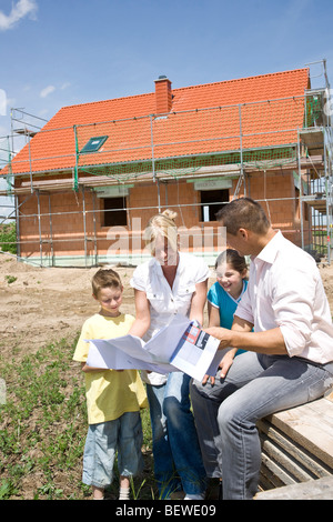 Family with two children looking at a plan in front of a house under construction - Stock Photo