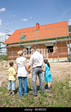 Family with two children looking at house under construction, rear view - Stock Photo