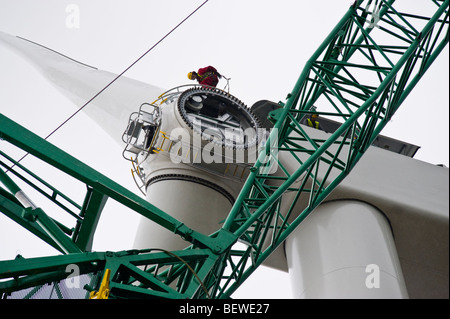 Engineers fitting blades lifted by crane to Nordex N90 wind turbine under construction in Newport South Wales UK - Stock Photo