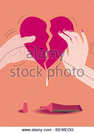 Man and woman gluing broken heart together - Stock Photo