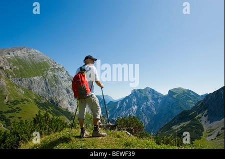 walking walker in the mountains alpes karwendel austria walking stick mountain hiker rambler 1 man lonely alone - Stock Photo
