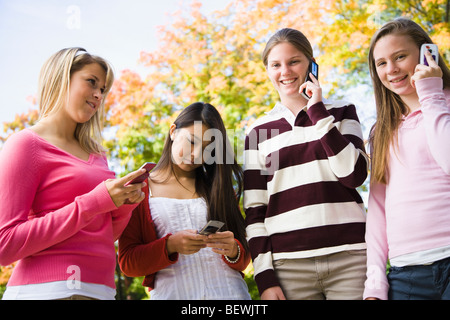 Four students using mobile phones - Stock Photo