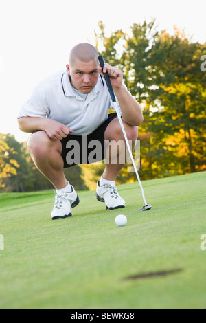 Man looking at hole in a golf course - Stock Photo
