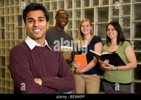 Group of young adults study together in a library - Stock Photo