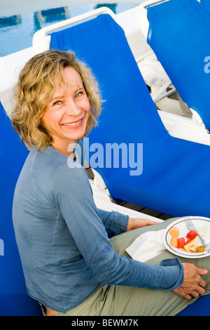 Portrait of a woman having fruit salad on a lounge chair, Tahaa, Tahiti, French Polynesia - Stock Photo
