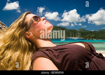 Woman leaning against a palm tree on the beach, Tahaa, Tahiti, French Polynesia - Stock Photo