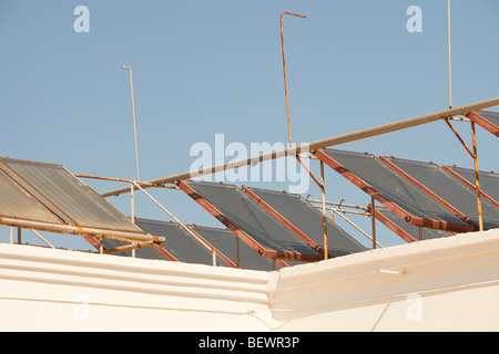 Solar water heating panels on the roof of a launderette in Teos, Turkey - Stock Photo