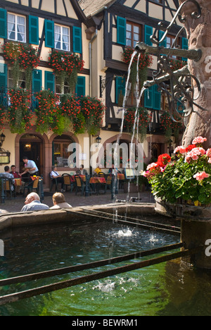 Flower decked fountain in central square with restaurant Hotel Du Chateau behind in Kaysersberg Alsace France - Stock Photo