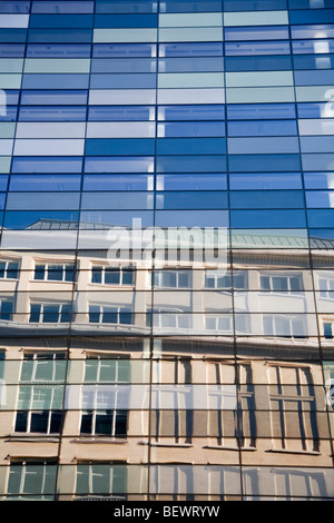 Old building reflected in glass skyscraper building City London England daylight summertime blue sky - Stock Photo