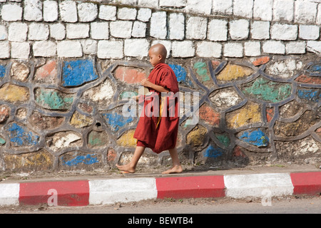 a young novice monk rings a chime during morning alms - Stock Photo