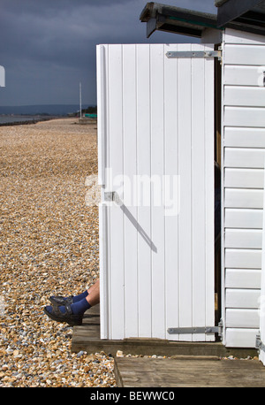 Man sitting in his Beach Hut Bexley on Sea East Sussex England - Stock Photo