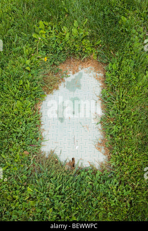 water valve plate overgrown with grass in public park, New Mexico, USA - Stock Photo
