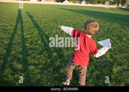 seven year old boy getting ready to throw his paper airplane in a park - Stock Photo