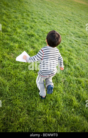 three year old Japanese boy runs through a park carrying his paper airplane - Stock Photo
