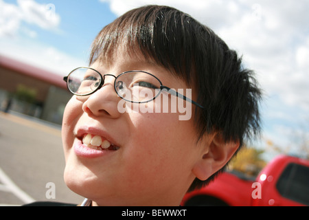happy Japanese boy wearing eye glasses smiling outdoors with blue sky in the background - Stock Photo