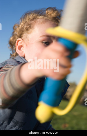 three year old boy lifting his sword, ready for pretend battle, foam sword weapon - Stock Photo