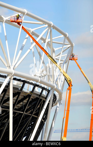 Men working from cherry picker hoists on the steel framework of the main 2012 Olympic stadium - Stock Photo