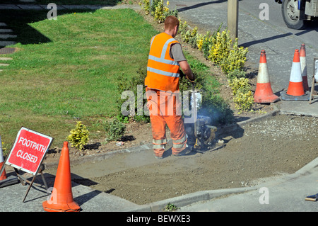 Workmen attending to footpath pavement repairs in residential street - Stock Photo