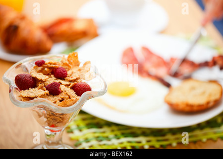 Delicious breakfast served. Corn flakes with berries, fried egg, bacon, toast, croissants, juice and fresh coffee. - Stock Photo