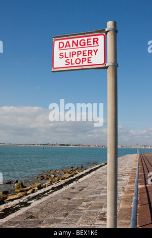 Danger Slippery Slope sign by the sea front in England, UK. - Stock Photo