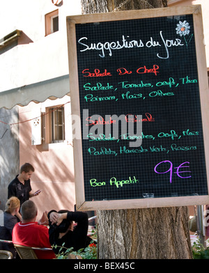 Simple inexpensive menu board waiter taking order with customers in alfresco Colmar restaurant Alsace France - Stock Photo