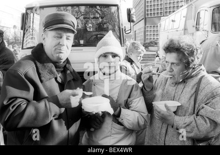 People from East Germany eating soup from free soup kitchen during a visit to West Berlin, November 1989 - Stock Photo