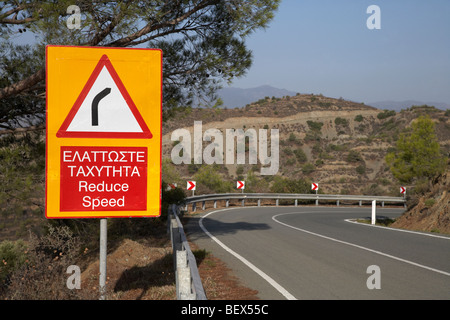 bilingual reduce speed dangerous bend sign on the f106 mountainside road near stavrovouni republic of cyprus europe - Stock Photo