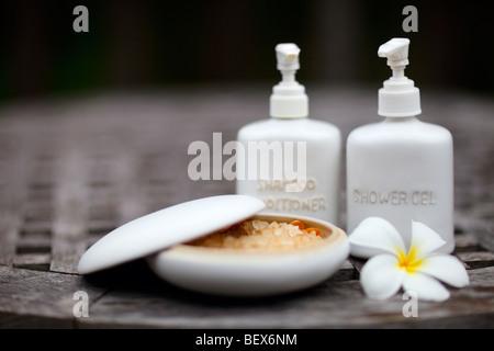Shampoo, shower gel, bath salt and frangipani flower - Stock Photo