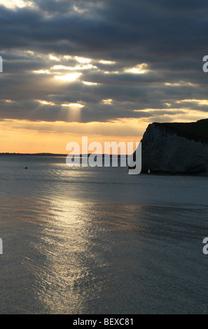 the sun reflects off the sea water at sunset at Durdle door in Devon, as the sun breaks through the dark clouds. - Stock Photo