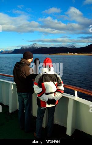 couple wearing warm arctic clothing admiring the norwegian coastline from ms nordkapp - Stock Photo