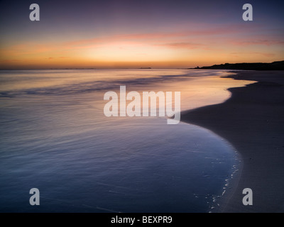 Pink pre-dawn light illuminates the sea at Budle Bay, Northumberland - Stock Photo