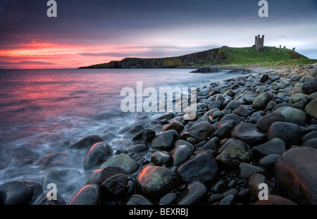 The pink pre-dawn light illuminates the sea and Graymare rocks at Dunstanburgh Castle. - Stock Photo