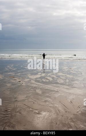 A female figure wandering on a beach in Cornwall UK - Stock Photo